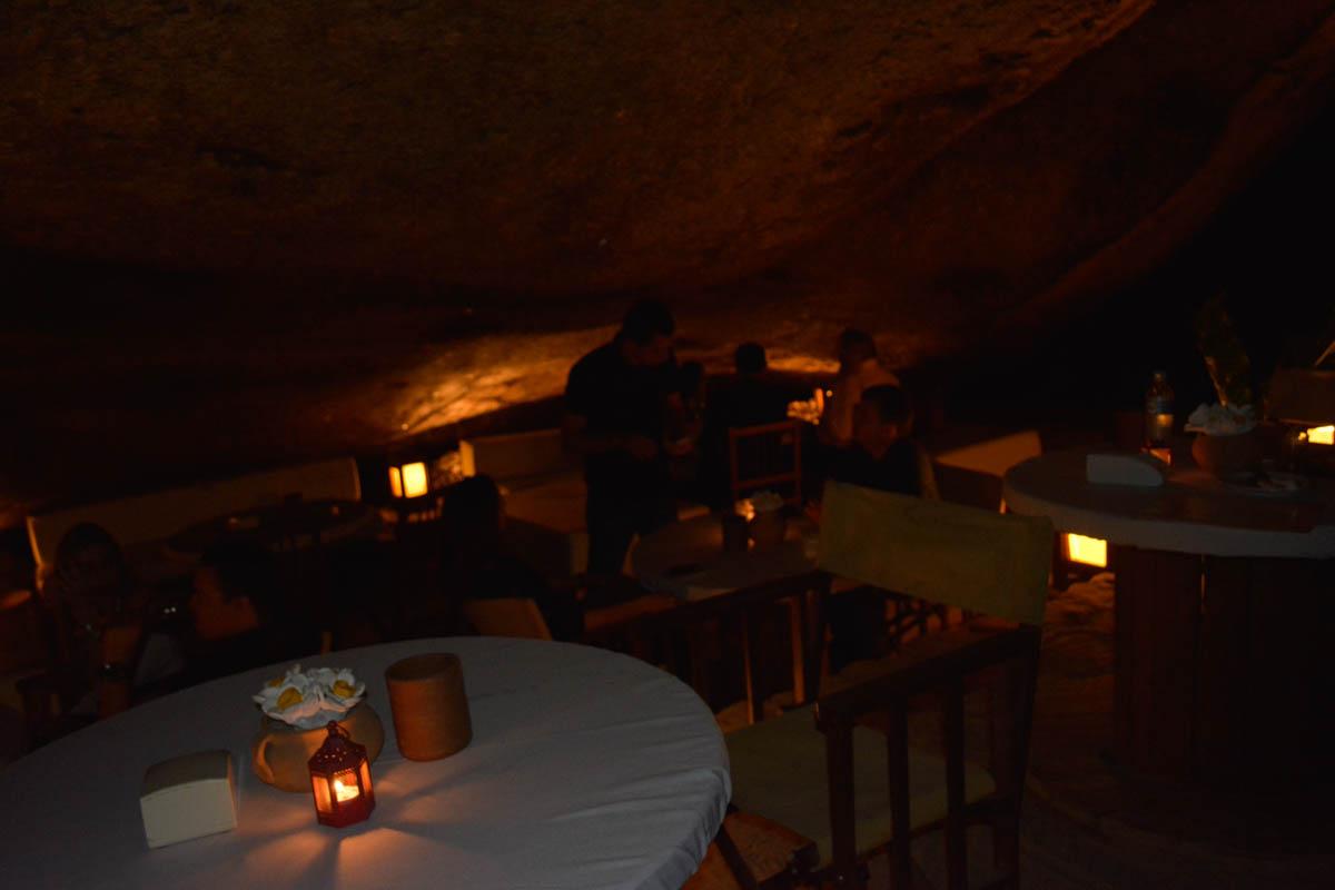 Comendo em um restaurante que fica debaixo de uma pedra